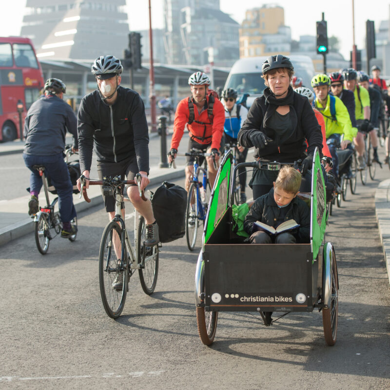 A line of commuting cyclists in a cycle lane, led by a woman with a child sitting in a cargo bike and reading a book