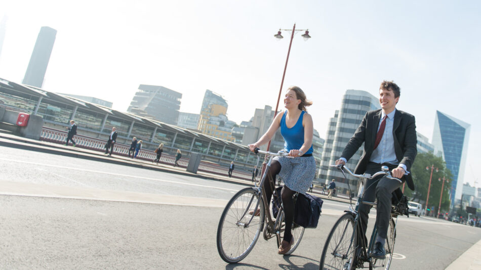 Two cyclists in office clothing cycling across Blackfriar's bridge using CS6