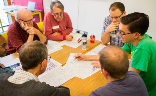 A group sitting around a table and discussing a map of cycle routes at the LCC AGM