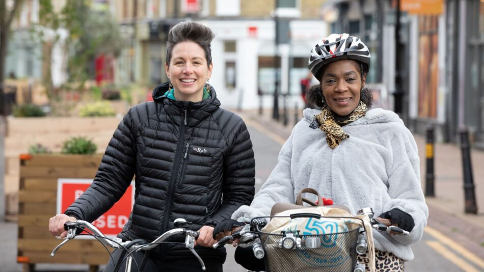 A pair of women smiling with their bikes and looking at the camera. This is one of our Cycle Buddies helping a new cyclist learn a route.