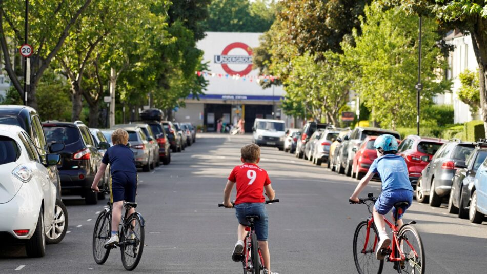 Three young children riding in an empty residential street by the Arsenal Tube Station