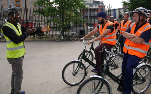 Group of freight drivers in orange hi-vis and on cycles receiving instruction from a cycle instructor