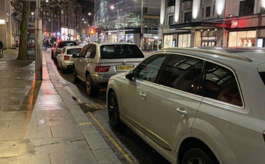 Cars parked along Kensington High Street