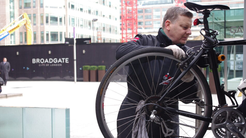 A man checking the pressure of a tyre