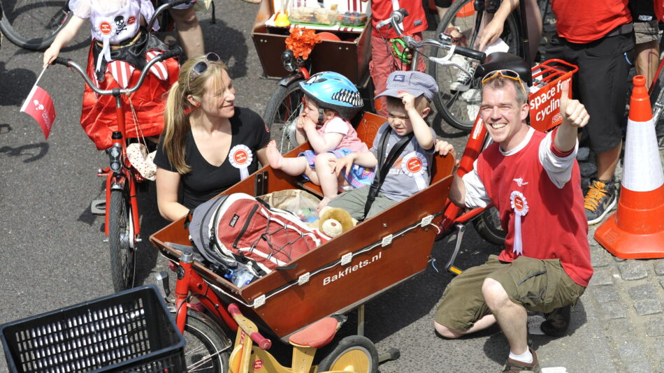 Two children sit in a cargo bike on a sunny day at a Space for Cycling event. Their parents are squatting next to the bike and the dad is giving a thumbs up to the camera.