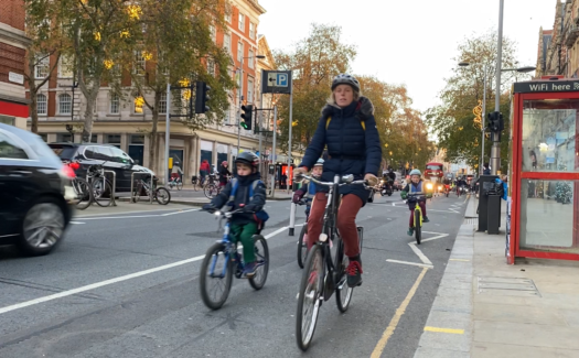 A mother and three children cycling in the Kensington High Street cycle lane