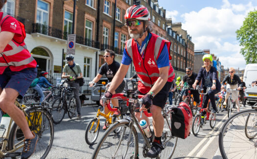 Cyclists in a Space for Cycling ride. In focus is a man in a red LCC vest.