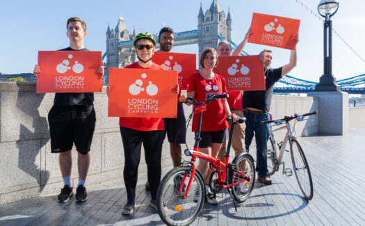 A group of LCC activists smiling and holding up red LCC signs. Tower Bridge is visible behind them.
