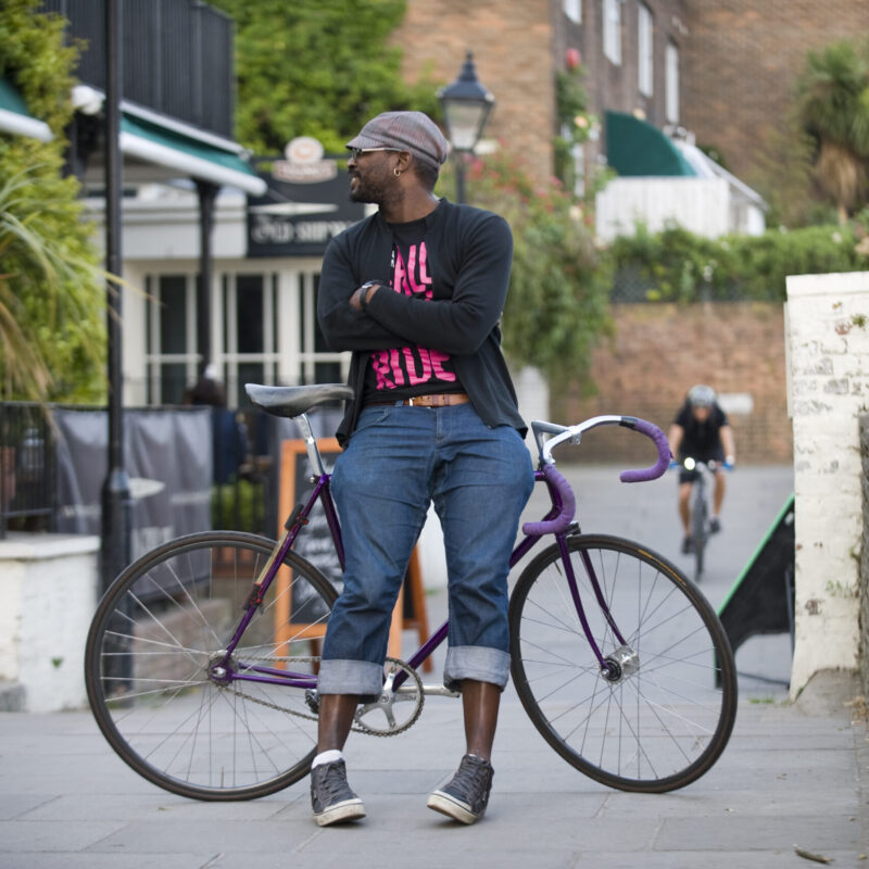 A man in casual clothing and a cap leaning against a fixie bike and smiling