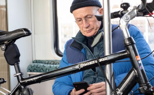 A man looking at his phone while taking a bike on public transport