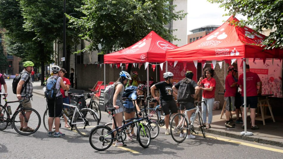Several cyclists stopped at an LCC tent at an event.