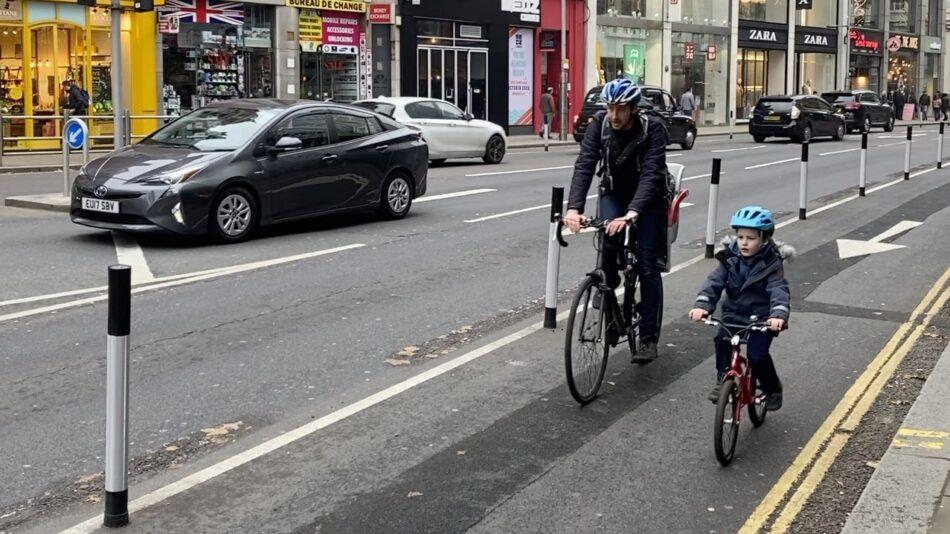 A father and son using a temporary cycle lane, marked off by wants, on Kensington High Street